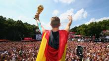 Fußballer Bastian Schweinsteiger hat sich eine Deutschland-Flagge umgebunden und jubelt mit WM-Pokal in der Hand in die Menge