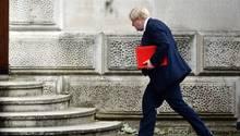 Boris Johnson mit einer roten Mappe unterm Arm