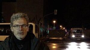Im Dunkeln steht ein Mann mit Brille und grauen Locken vor einer von der Polizei bewachten Absperrung