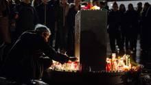 Ein Mann zündet eine Kerze auf dem Marktplatz an. Bei Schüssen in Halle sind zwei Menschen getötet worden