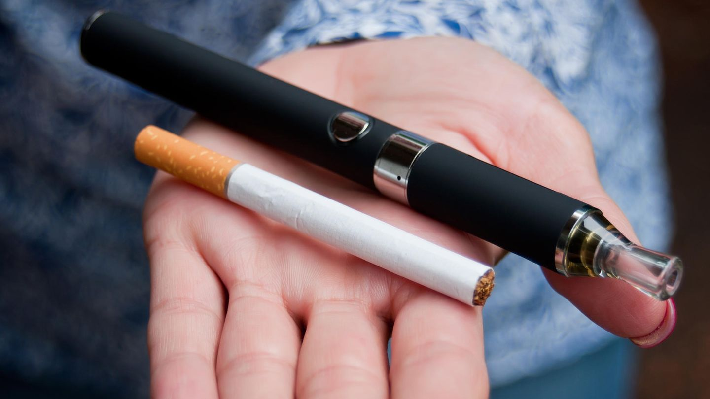 E-Zigarette: Eine Frau hält eine Zigarette und eine E-Zigarette in der Hand