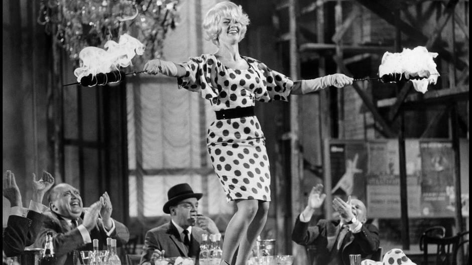 """Liselotte Pulver als Sexbombe """"Fräulein Ingeborg"""" in Billy Wilders Ost-West-Satire """"Eins, zwei, drei"""". Die Szene, in der sie die Hüfte schwingend auf dem Tisch tanzte, machte sie zur Schweizer Antwort auf Marilyn Monroe.Der Film brachte der in Bern geborenen Schauspielerin 1961 weltweit Anerkennung ein. Zu dieser Zeit war sie in Deutschland bereits ein Publikumsliebling. Die """"Liselotte aus der Schweiz"""", wie ein Reporter sie nannte, verzückte mit ihrem Charmedas Publikum. Ihr ansteckendes Lachen wurde dabei zu Pulvers Markenzeichen."""