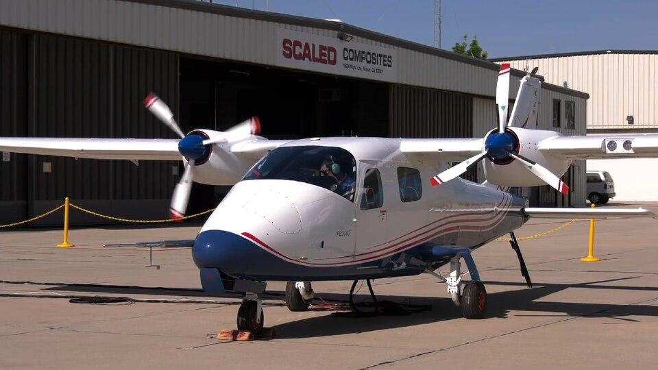 Eine zweimotorige Propellermaschine steht mit rotierenden Propellern vor einem Flugzeughangar