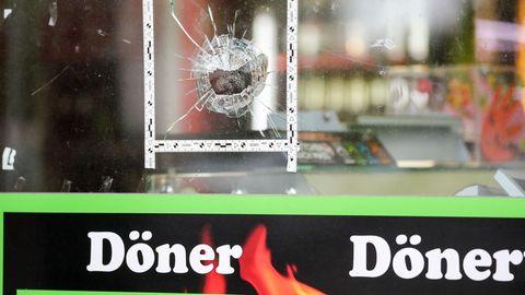 Markierungen der Polizei kleben um einen Einschuss in der Schaufensterscheibe eines Dönerladens in Halle