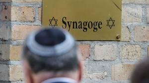 Ein Mann mit Kippa besucht den Tatort an der Synagoge