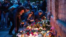 Trauernde legen an der Mauer der Synagoge Blumen nieder und zünden Kerzen an