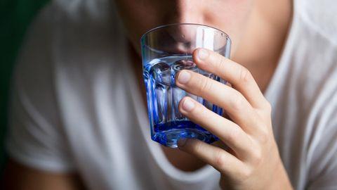 Ein Mann schluckt mit Wasser eine Pille herunter