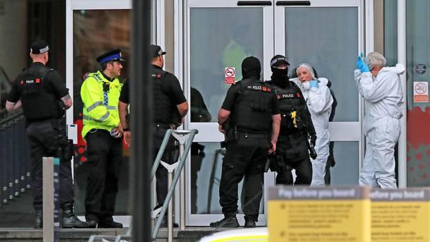 Polizeibeamte und Gerichtmediziner stehen vor einem Eingang eines Einkaufszentrums