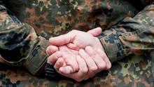 Ein Soldat hält in der Julius-Leber-Kaserne auf einem Übungsplatz seine Hände hinter dem Rücken