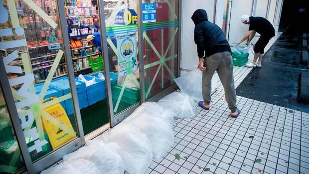 Taifun Hagibis Tokio: Mitarbeiter eines Supermarkts treffen Maßnahmen, um ihren Laden vor den Fluten zu schützen