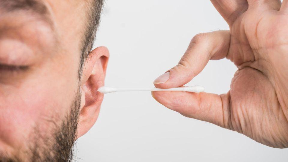 Spinne im Ohr: Ein Mann benutzt ein Wattestäbchen