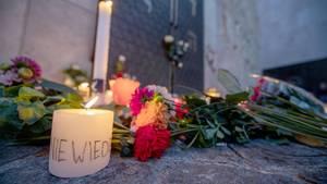 Menschen legen an der Mauer der Synagoge Blumen und Kerzen nieder.