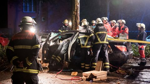 Hamburg: Einsatzkräfte der Feuerwehr arbeiten nach einem Verkehrsunfall an einem Autowrack