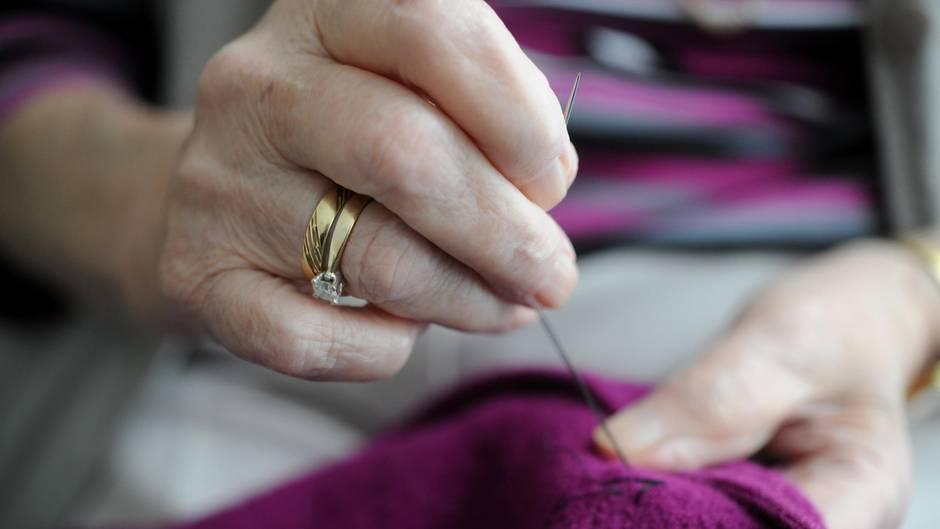 Eine Seniorin näht an einer Jacke