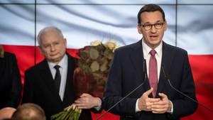 Nach den Wahlen spricht PremierministerMateusz Morawiecki (r.) zu Parteimitgliedern der PiS