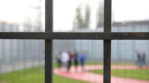 Hinter einem Gitter laufen am Gefängnisinsassen einer Justizvollzugsanstalt
