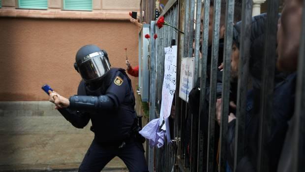 Am 1. Oktober 2017: Ein Angehöriger der spanischen Polizei verschafft sich Zugang zu einem Wahllokal in Katalonien