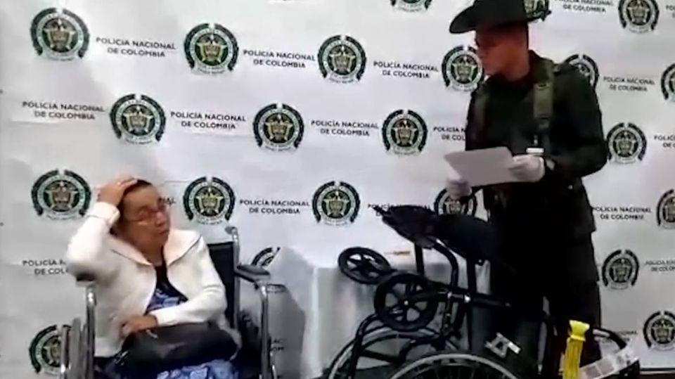 Eine alte Frau sitzt im Rollstuhl, während ein Mann in Tarnanzug und Gummihandschuhen neben ihr steht