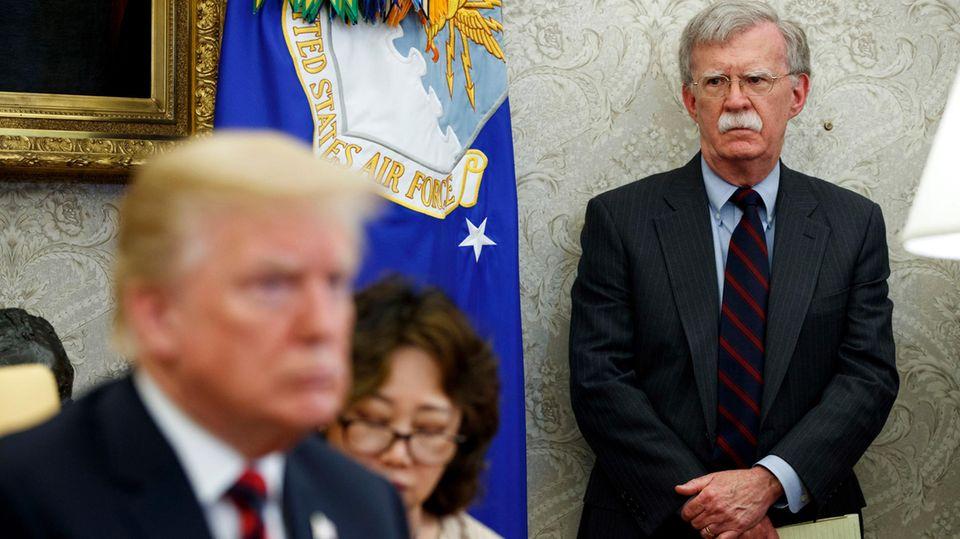 John Bolton (r.) beäugtUS-Präsident Donald Trump mit kritischem Blick