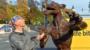 Aktionskünstler Rainer Opolka steht an einem seiner vier Bronzewölfe gegenüber des jüdischen Friedhofs in Halle