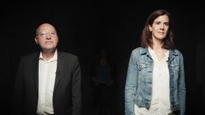 Vor schwarzem Hintergrund steht links ein Mann mit Glatze und runder Brille, rechts eine Frau mit schulterlangen braunen Haaren