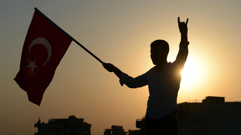 Ein Mann im türkischenAkcakale schwenkt eine Nationalflagge