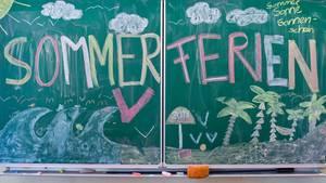 """Auf einer Schultafel steht in bunten Buchstaben mit Kreide geschrieben """"Sommerferien"""""""