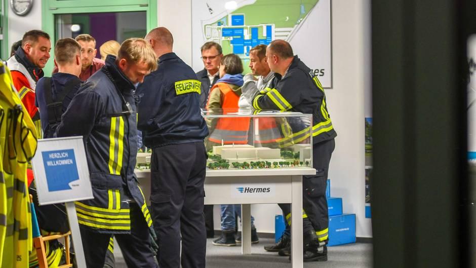 Sachsen-Anhalt, Haldensleben: Mitarbeiter der Feuerwehr stehen im Hermes Logistikzentrum
