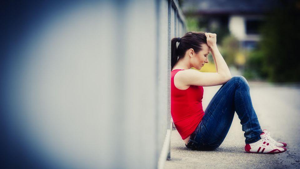 Hochstapler-Syndrom – unglückliche junge Frau sitzt an Brückengeländer