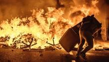 Barcelona: Ein Demonstrant wirft einen Mülleimer auf eine brennende Barrikade