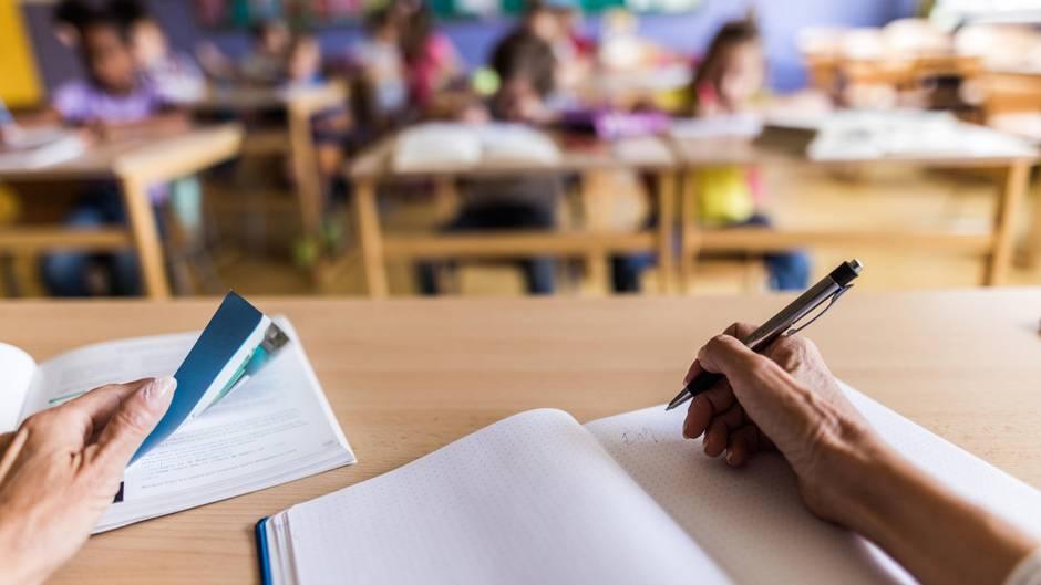 Eine Lehrerin sitzt vor einer Grundschulklasse