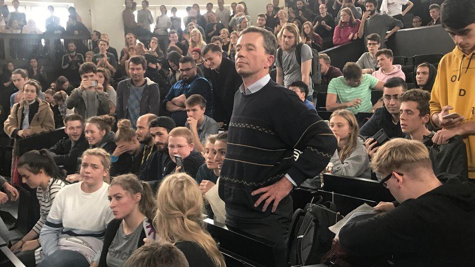 Bernd Lucke steht zwischen den Studierenden