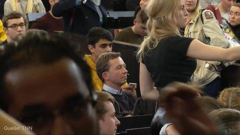 Ein Mann mit braunem Seitenscheitel sitzt in einem vollen Hörsaal zwischen sitzenden und stehenden Studierenden
