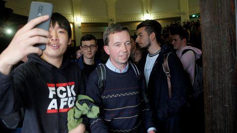 """Ein Student im schwarzen """"FCK AFD""""-Kapuzenpullover macht mit seinem Smartphone ein Selfie mit Bernd Lucke"""
