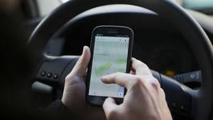 Ein Mann nutzt Google Maps am Steuer (Symbolfoto). Ein Ort in Italien warnt