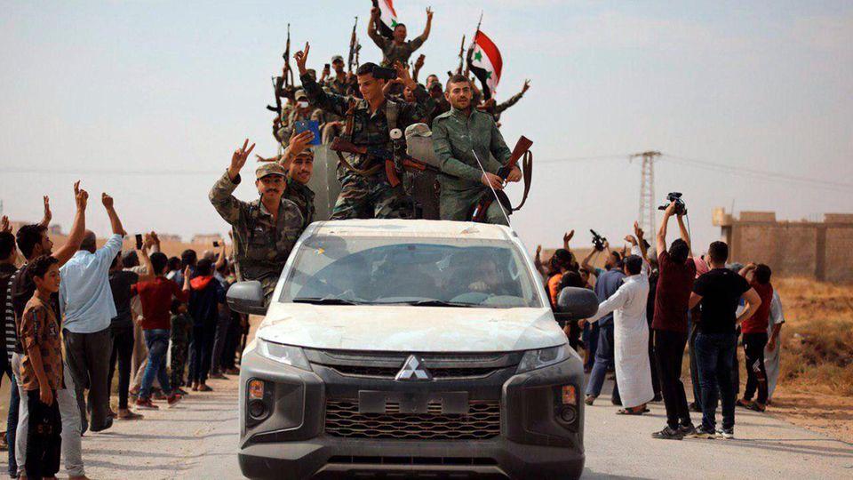 Syrische Soldaten auf einem Transporter. Zivilisten winken ihnen zu.