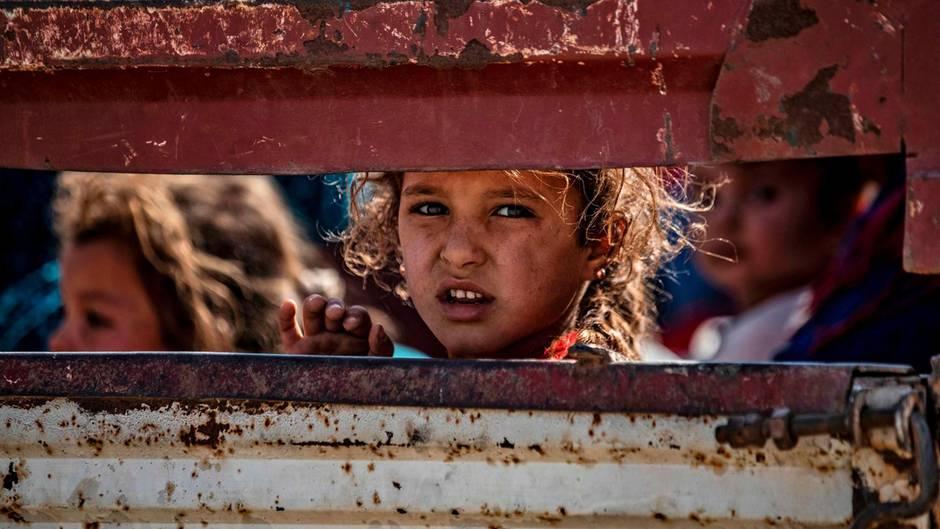 Ein Kind blickt durch den Spalt eines Lastwagens