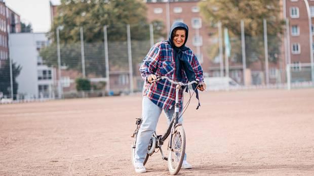 Flüchtlingsfrauen lernen Fahrrad fahren auf dem Sportplatz von SC Urania in Hamburg Barmbek