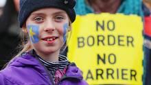 Ein Mädchen mit aufs Gesicht gemalten EU-Sternen lächelt