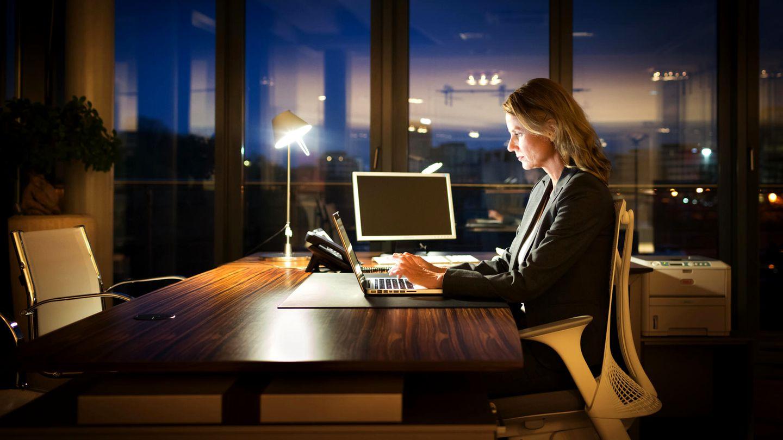 Frau sitzt abends im Büro