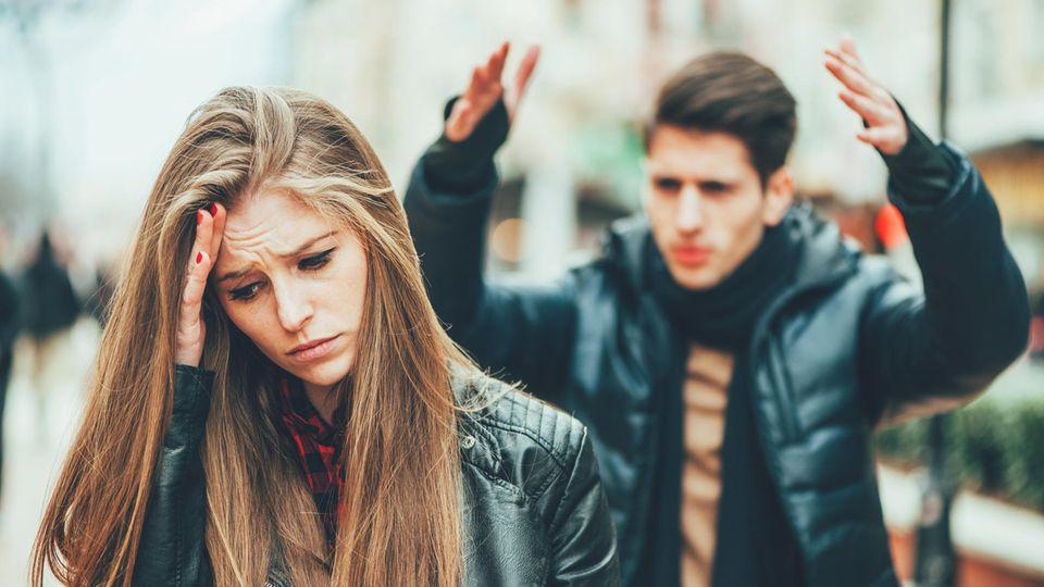 Frau schaut traurig und genervt, während ihr Partner im Hintergrund wütend zu sein scheint