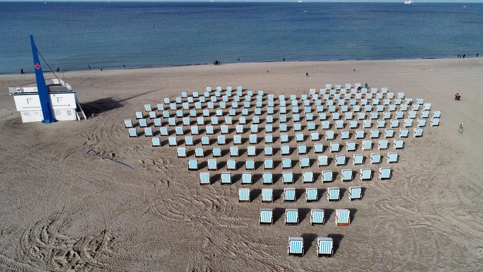 Warnemünde, Deutschland. Ein Vermieter hat seine Strandkörbe am schönen Strand des Ostseebadesin Form eines Herzen aufgestellt. Er will sich damit insbesondere bei den Urlaubernbedanken, die im bekannten Fünf-Sterne-HotelNeptun wohnen und auf das Strandkorb-Herzblicken.