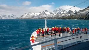 Auf dem Vorschiff dabei: Passagiere auf einem Kreuzfahrtschiff in der Antarktis