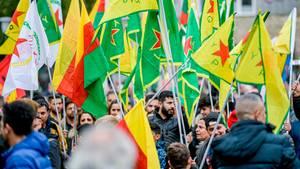 Teilnehmer einer Demonstration der Kurden schwenken Fahnen der YPG