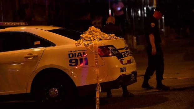 Im Dunkeln sucht ein Polizist am Heck eines Polizeiwagens nach Spuren auf der Straße