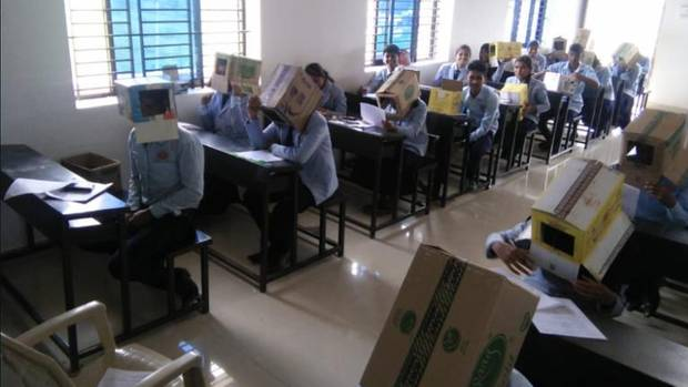 Schüler tragen bei einer Prüfung Kartons auf den Köpfen