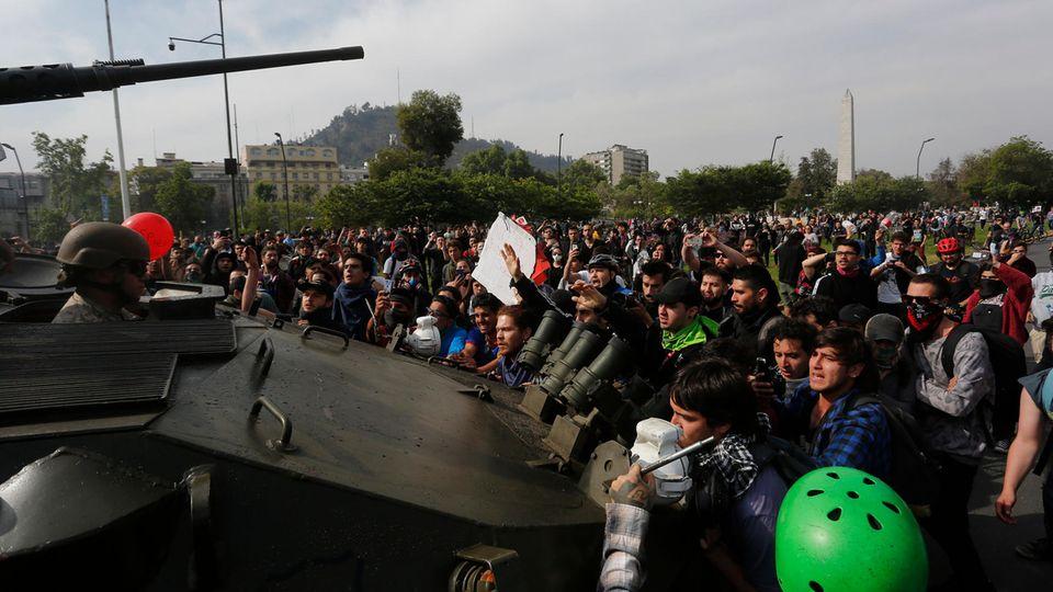 Regierungsgegner stellen sich in Santiago einem Militärfahrzeug in den Weg