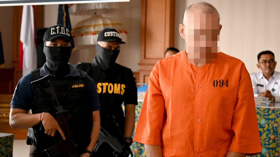 Ein Mann steht in orangenem Hemd vor zwei schwer bewaffneten Polizisten