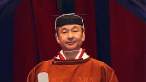 Ein Japaner steht in traditionellem, rotbraunem Gewand vor einer hölzernen Wand