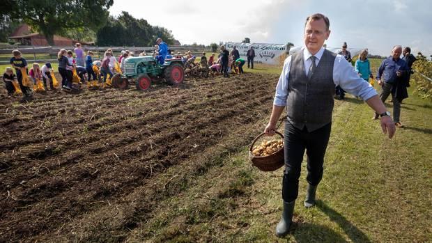 Ministerpräsident Ramelow mit einem Korb selbst geernteter Kartoffeln auf einem Feld in Heichelheim